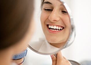 Patient looking at teeth in mirror
